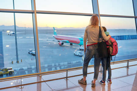Airport passengers family mother and daughter child looking at planes in panoramic window