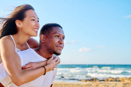 Young beautiful having fun couple on the sea background