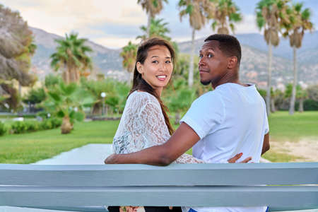 Beautiful young multi-ethnic couple sitting together on a bench in a tropical park