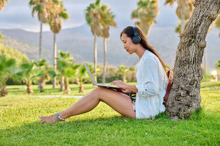Young woman in headphones working on a laptop outdoors.
