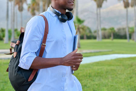 Outdoor portrait of young man with laptop headphones and backpack