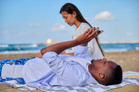 Young beautiful couple having a rest on the beach, man with smartphone