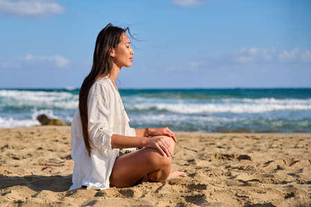 Young beautiful woman in lotus position meditating on the beach