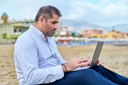 Serious confident mature man with laptop outdoors