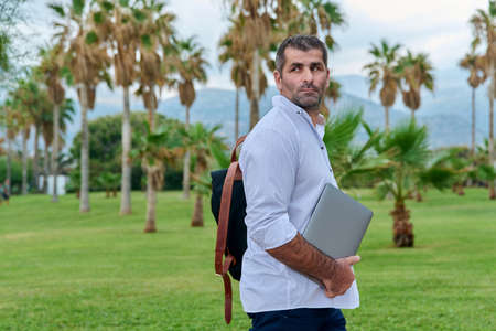 Portrait of serious confident mature man with laptop outdoors