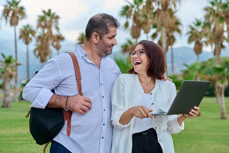 Middle-aged man and woman looking into the laptop screen outdoors