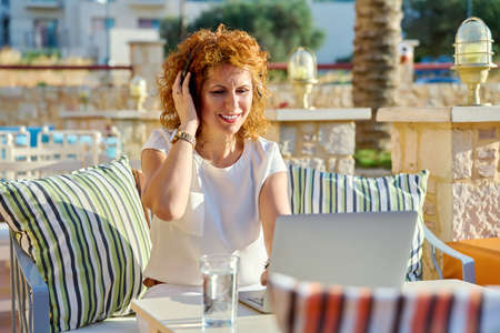 Positive smiling woman working with laptop outdoors.