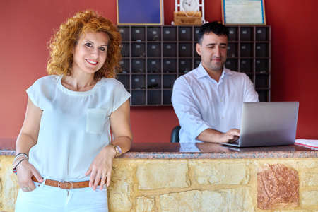 Small family hotel business, couple of hotel owners working at the front desk