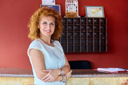 Portrait of confident positive woman hotel business owner