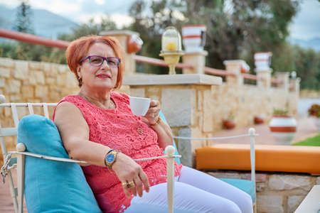 Portrait of beautiful elderly 70s woman relaxing with cup. Smiling senior female with glasses sitting in an outdoor cafe enjoying coffee. Beauty, age, health, pensioner, retired older people concept Stock fotó