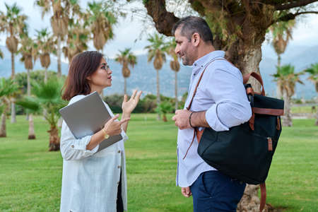Mature man and woman business colleagues talking outdoors