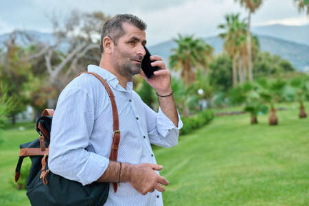 Mature business man talking on the phone outdoors