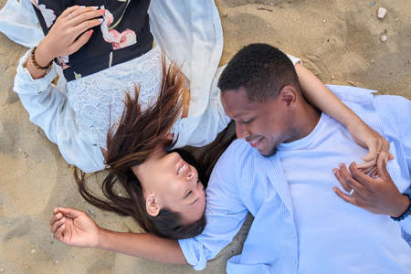 Top view of a young multiracial couple in love on the sand