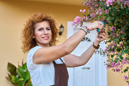 Woman in garden with pruner caring for flowering bush