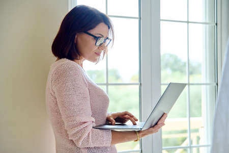 Mature businesswoman in glasses with laptop in her hands near window Stock fotó