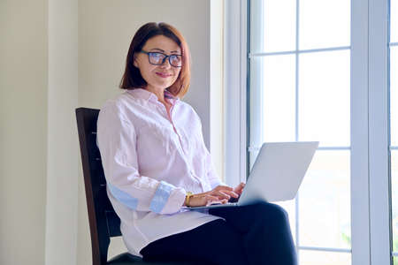 Business woman sitting on a chair with a laptop looking at the camera