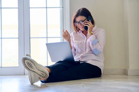 Business middle aged woman sitting on the floor with a laptop talking on a mobile phone
