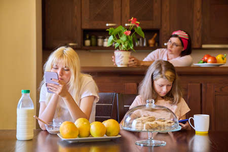 Family, girls, children eating at the table in the kitchen