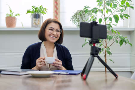 Middle aged business woman, counselor, mentor in a video meeting, using a smartphone Stock fotó