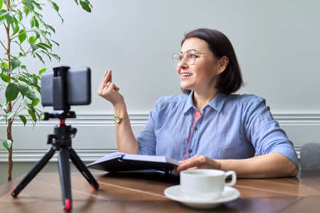 Middle-aged woman teacher, businesswoman working online using smartphone