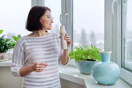 Middle-aged woman drinking milk drink, liquid yogurt in bottle, at home near window