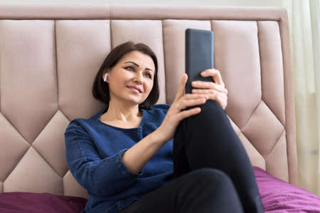 Smiling middle-aged woman in headphones looking into a smartphone, lying in bed at home