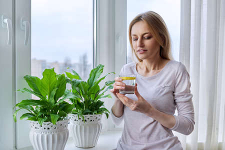Middle-aged woman drinking lemon water at home near the window