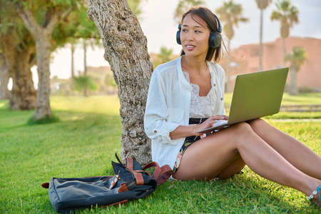 Young woman in headphones with laptop sitting on the grass in the park
