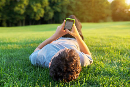 Guy teenager lying on grass with smartphone. Stock fotó