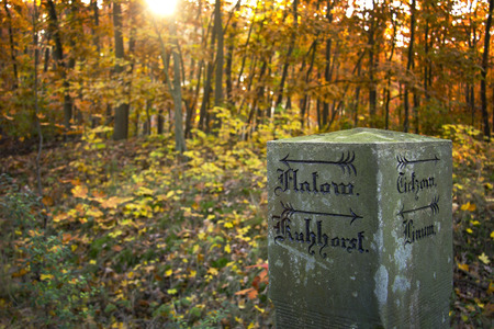 milepost: Historical mile marker or milepost with old german inscription in the autumn forest, was seen in Brandenburg, Havelland, Germany Stock Photo