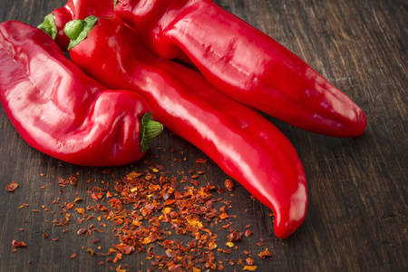 crushed red peppers: Four fresh red sweet paprika peppers on the wooden table with spicy chilli. Stock Photo