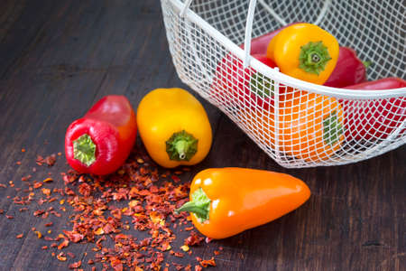 crushed red peppers: Fresh sweet (paprika) peppers on the wooden table with little metal basket and  spicy chilli.