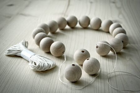 beechwood: Wooden beads on a wooden background with thread Stock Photo