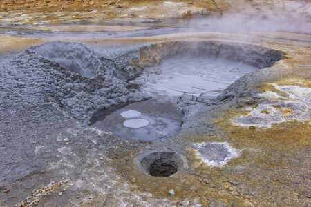 View to a mudpot, or mud pool. It is a sort of acidic hot spring, or fumarole, with limited water. It usually takes the form of a pool of bubbling mud. Iceland.