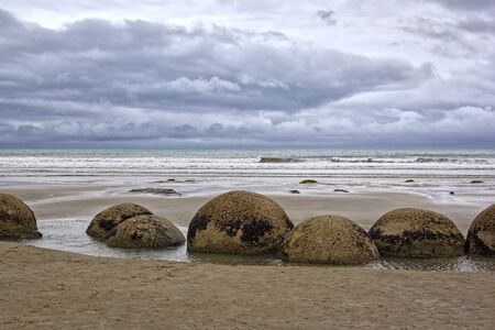 The Moeraki Boulders are unusually large and spherical boulders lying along a stretch of Koekohe Beach on the wave-cut Otago coast of New Zealand between Moeraki and Hampden.