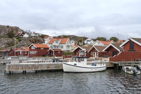 Old buildings and cottages, boats at the skerry coast near Bovallastrand (Sweden). Typical situation for the skerry coast. Archivio Fotografico