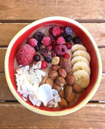 Gesundes Frühstück, frisch zubereitet ist die Smoothie Bowl. Zutaten sind verschiedene Früchte wie Brombeeren und Banane und Joghurt oder Brei.