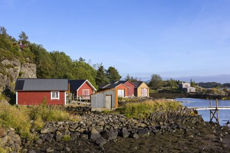 Several fishermen's cabins and boathouses by the sea. A typical Norwegian coastal landscape. Seen here near Alversund, on the island of Radoy, near Bergen. Archivio Fotografico