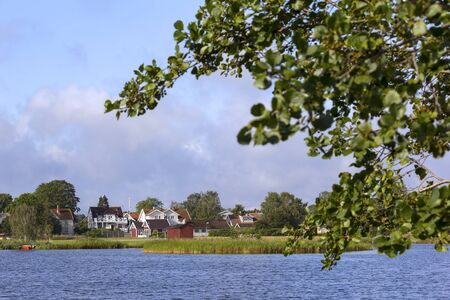 View of a small but typical Swedish village, near the Baltic Sea coast. One sees a small bay with reeds and the houses on the shore.