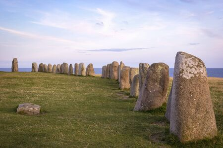 View to Ales stenar. It is a megalithic monument in Scania in southern Sweden. It is a stone ship, oval in outline, with the stones at each end markedly larger than the rest. It is 67 m long formed by 59 large boulders, weighing up to 1.8 tonnes each.