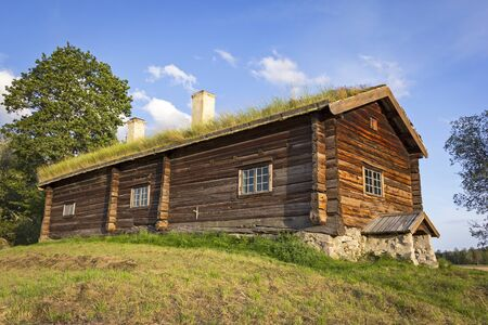 View of a very old log cabin. It stands on a small hill, in the middle of a meadow. You can see a traditional nordic architecture. Stock Photo