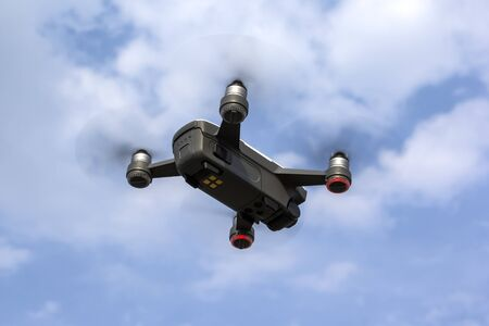 A small drone flies in the sky. Flying such drones is a hobby.