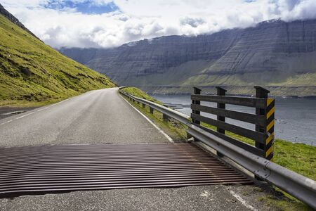 A lonely country road in the Faroe Islands meanders along the ocean. Typical are the grids on the road so that the sheep don't run along it.