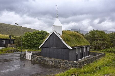 View of a small church, on the Faroe Islands. Typical is the wooden construction and the grass-covered roofs. It is a rainy day, as so often in the north. Standard-Bild