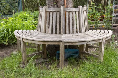 View of a wooden round bench in an allotment garden. There a wonderful place to rest has been created. Standard-Bild