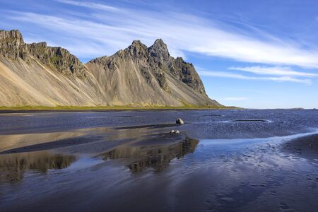 View to the famous Vestrahorn and Stokksnes. Stokksnes is a headland on the southeastern Icelandic coast, near Hofn and Hornafjordur. There is a light house on the tip of the land. Standard-Bild