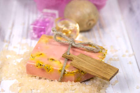 Slice of natural handmade soap, made with fresh ingredients, (orange, herbs) and bath salts.