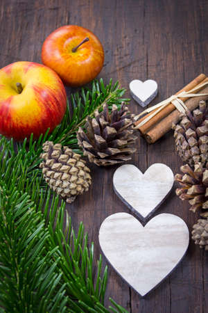 At an old table the Christmas decoration is placed ready: pine cones, apples, wooden hearts, pine green, cinnamon sticks.