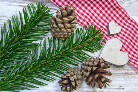 At an old table the Christmas decoration is placed ready: pine cones, apples, wooden hearts, pine green.