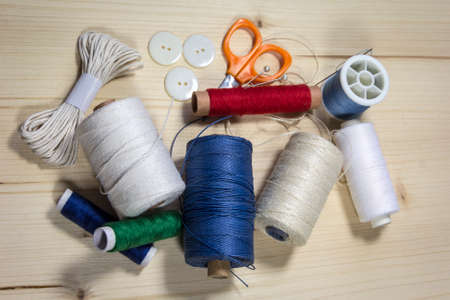 View of sewing thread and accessories on a table, string, thread rolls, pins and scissors.